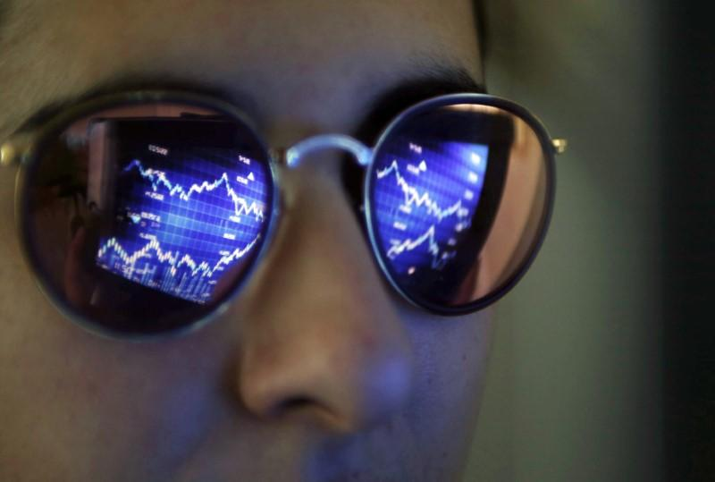 A computer screen showing stock graphs is reflected on glasses in this illustration photo taken in Bordeaux, France, March 30, 2016. Regis Duvignau