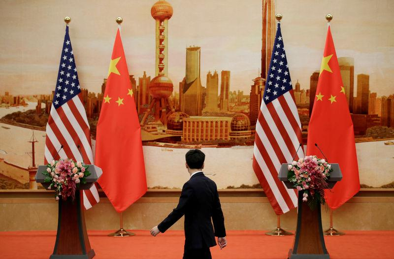 A staff member walks past U.S. and Chinese flags placed for a joint news conference by U.S. Secretary of State Mike Pompeo and Chinese Foreign Minister Wang Yi at the Great Hall of the People in Beijing, China June 14, 2018. Jason Lee