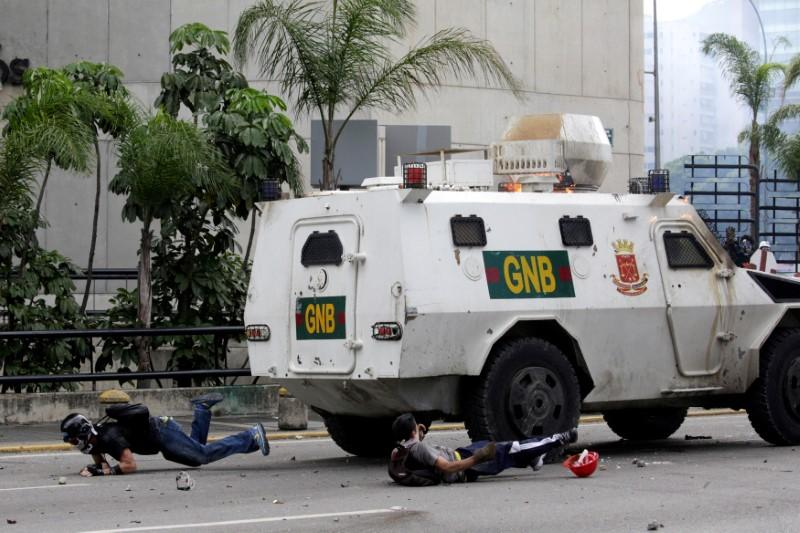 Demonstrators fall on the ground after being hit by a riot police armoured vehicle while clashing with the riot police during a rally against Venezuelan President Nicolas Maduro in Caracas, Venezuela, May 3, 2017. Marco Bello