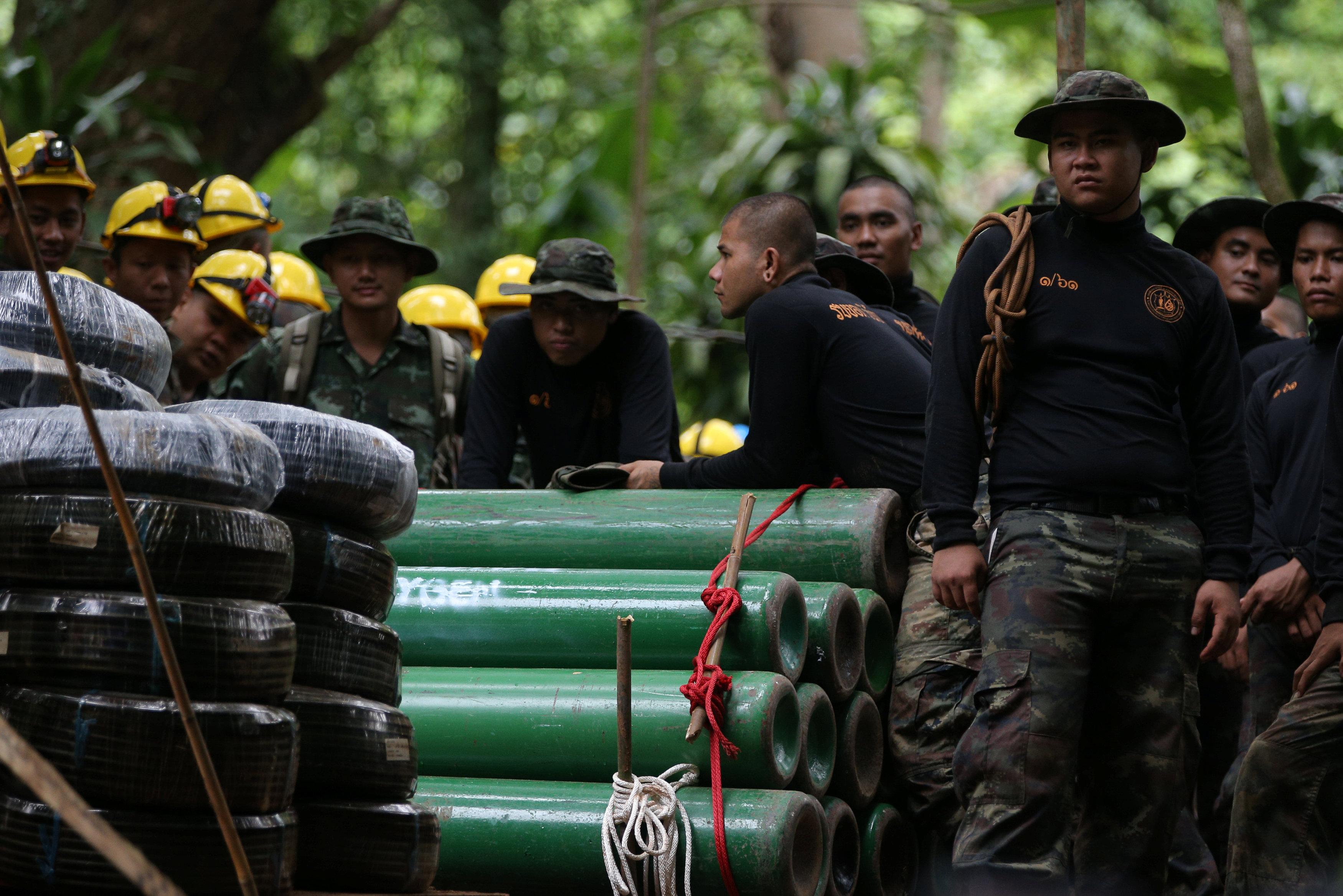 Military personnel gather near oxygen tanks near the Tham Luang cave complex, where 12 boys and their soccer coach are trapped, in the northern province of Chiang Rai, Thailand, July 6, 2018. Athit Perawongmetha