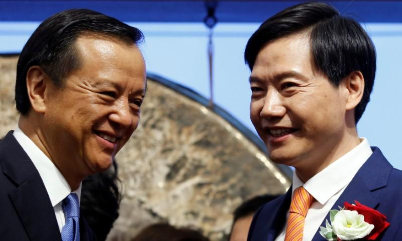 Xiaomi founder, Chairman and CEO Lei Jun (R) chats with Hong Kong Exchanges and Clearing Chief Executive Charles Li during the listing of the company at the Hong Kong Exchanges in Hong Kong, China July 9, 2018.   Bobby Yip