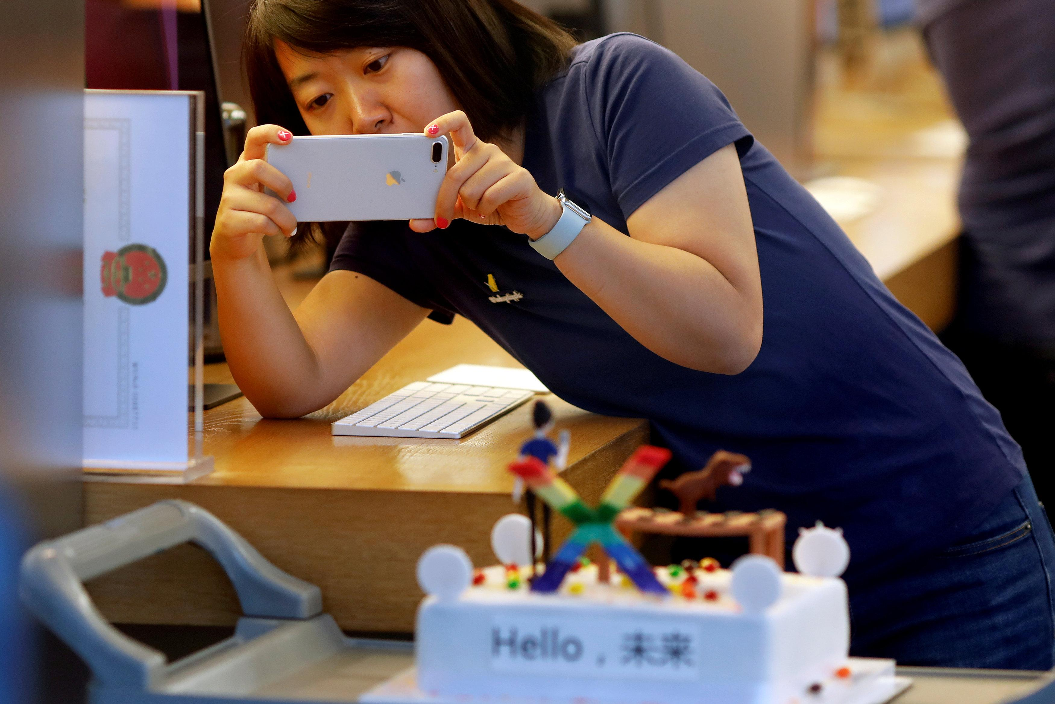 A member of Apple staff takes pictures as new iPhone X begins to sell at an Apple Store in Beijing, China November 3, 2017. Damir Sagolj