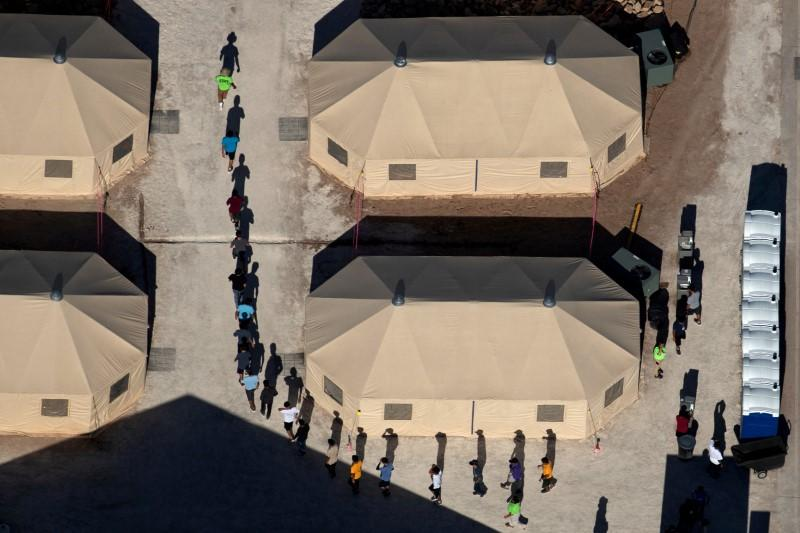 Immigrant children are led by staff in single file between tents at a detention facility next to the Mexican border in Tornillo, Texas, U.S., June 18, 2018. Picture taken June 18, 2018. Mike Blake
