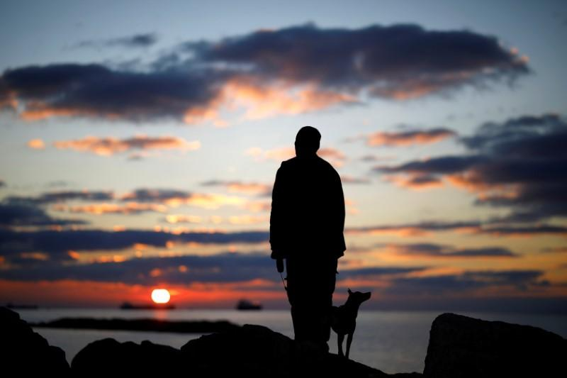 A man watches the sunset with his dog on a breakwater. Amir Cohen