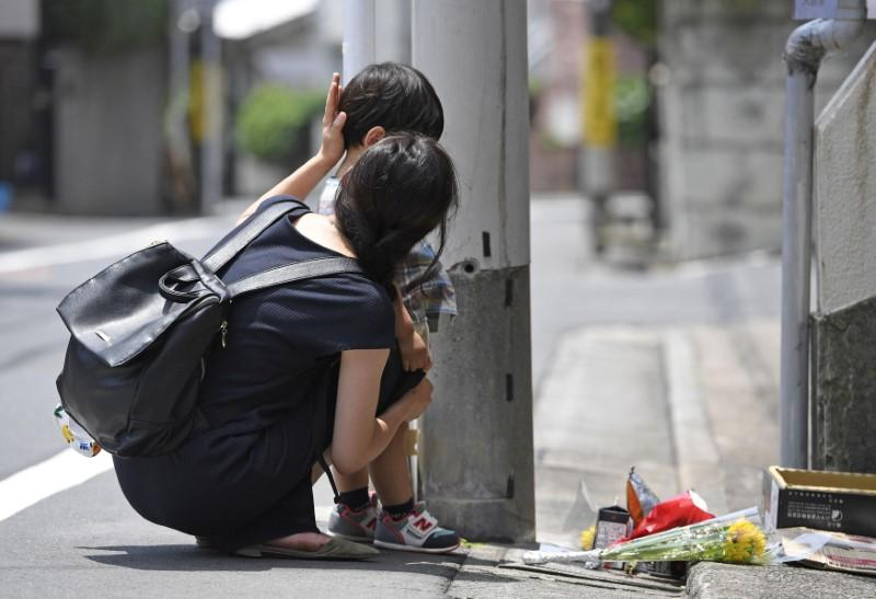 A mother and her child mourn for Yua Funato in front of an apartment where she died in Tokyo, Japan, in this photo taken by Kyodo June 26, 2018. Kyodo/via