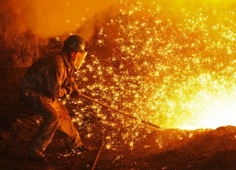 An employee works next to molten iron at a steel mill of Dongbei Special Steel in Dalian, Liaoning province, China July 17, 2018. Stringer