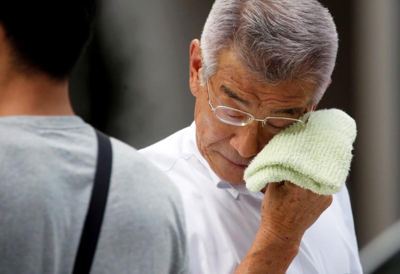 A businessman wipes his face while walking on a street during a heatwave in Tokyo, Japan July 23, 2018.  Issei Kato