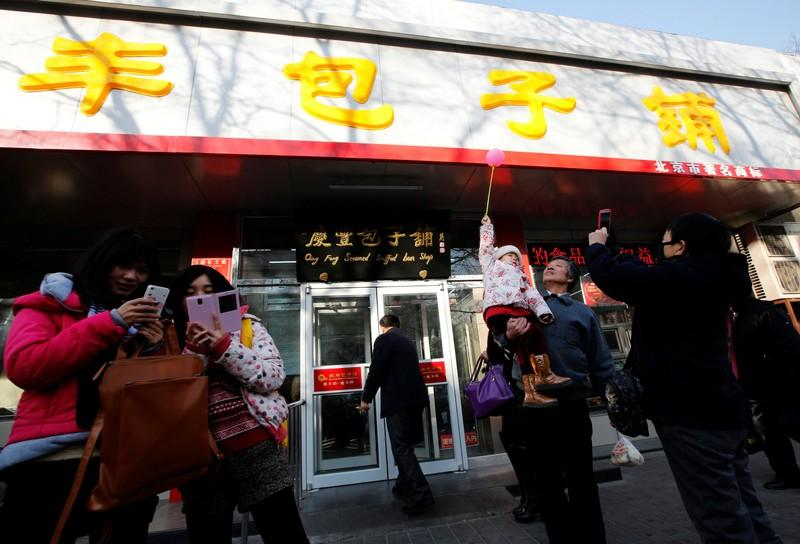 Visitors take pictures for remembrance at the Qing-Feng steamed buns restaurant where Chinese President Xi Jinping visited and dined at on Saturday, in Beijing, December 29, 2013.  Kim Kyung-Hoon