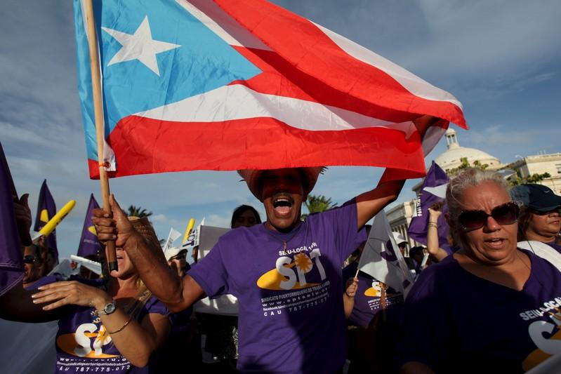 A member of a labor union shouts slogans while holding a Puerto Rico flag during a protest in San Juan September 11, 2015. Reuters/Alvin Baez