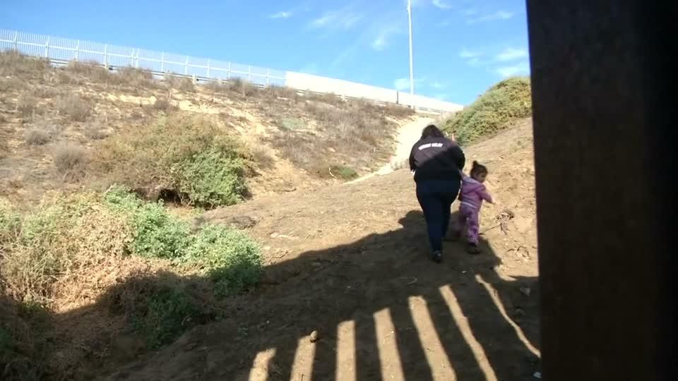 Migrants, including woman with young daughter, breach U.S. border