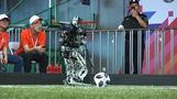 Falling and scoring, robots compete on football pitch