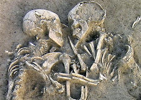 A pair of human skeletons lie entwined at an Neolithic archaelogical dig site near Mantova, Italy, in a photo released February 6, 2007. REUTERS/Enrico Pajello/Handout