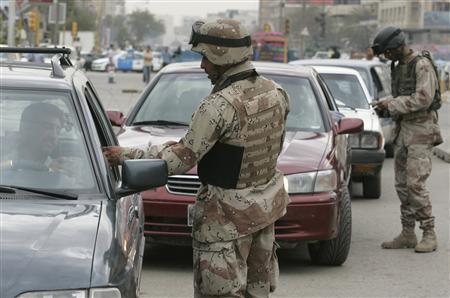 Iraqi soldiers check the identification papers of motorists in Baghdad, March 28, 2007. REUTERS/Namir Noor-Eldeen