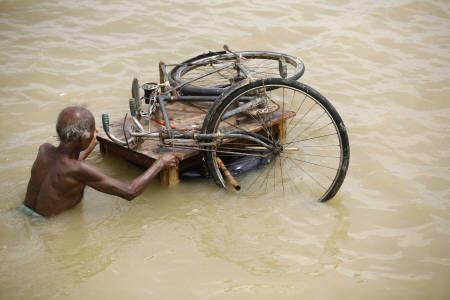 A man transports his bicycle through a flood-hit area of Darbhanga district, about 200 km north from Patna, August 8, 2007. Climate change might get some blame for South Asia's catastrophic floods, but government ineptitude has dramatically magnified the misery, aid groups and experts say. REUTERS/Jayanta Shaw