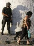 <p>Жительница одного из бедных районов Рио-де-Жанейро проходит мимо сотрудника бразильской полиции 14 февраля 2007 года. Вертолет, перевозивший Санта Клауса на один из детских праздников, был обстрелян наркоторговцами в одном из районов Рио-де-Жанейро, сообщил источник в полиции во вторник. (REUTERS/Bruno Domingos)</p>
