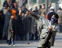 """<p>Сторонник убитой Беназир Бхутто кидает камень в сторону индийской полиции в Шринагаре, столице индийской части штата Кашмир, 28 декабря 2007 года. Индия привела пограничные войска в """"состояние наивысшей бдительности"""" после убийства лидера пакистанской оппозиции Беназир Бхутто, повергнувшего соседнюю в состояние хаоса, который угрожает перекинутся на соседние государства. (REUTERS/Fayaz Kabli)</p>"""