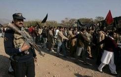 <p>Пакистанский полицеский наблюдает за демонстрацией сторонников Беназир Бхутто в Исламабаде , 29 декабря 2007 года. Сторонник погибшего в четверг лидера пакистанской оппозиции Беназир Бхутто был убит неизвестными в субботу утром, став очередной жертвой волны насилия, захлестнувшей страну в преддверии парламентских выборов. (REUTERS/Faisal Mahmood)</p>
