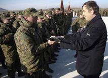 <p>Президент Грузии Михаил Саакашвили вручает военнослужащему новую винтовку М-4 на церемонии открытия новой военной базы в Гори 18 января 2008 года. (REUTERS/Irakli Gedenidze/Pool)</p>