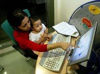 <p>Una mamma indiana seduta in un internet caffè di Calcutta con in braccio sua figlia. REUTERS/Jayanta Shaw</p>