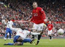 <p>Il bomber del Manchester United Wayne Rooney mentre dribbla Sol Campbell del Portsmouth (sinistra). La squadra inglese dei Red Devils dovrà affrontare la Roma ai quarti di finale della Champions League. REUTERS/Darren Staples (BRITAIN)</p>