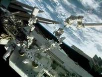 <p>L'astronauta Mike Foreman (sinistra) lavora al robot canadese Dextre al di fuori della Stazione spaziale mentre il compagno Rick Linnehan (destra) si lascia trasportare dal braccio meccanico. REUTERS/NASA TV</p>