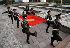 <p>Киргизские военнослужащие несут флаг своей страны в Бишкеке 1 ноября 2006 года. Бишкекский гарнизонный военный суд приговорил двух действующих и двух бывших офицеров контрразведки к длительным срокам заключения, признав виновными в шпионаже в пользу России и разглашении гостайны, сообщил Рейтер адвокат одного из осужденных. (REUTERS/Vladimir Pirogov)</p>