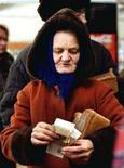 <p>Жительница белорусского села Краснополье считает деньги после покупки хлеба, 20 ноября 1999 года. Белорусский президент Александр Лукашенко во вторник пообещал жителям страны удвоить - в долларовом выражении - среднюю зарплату к 2011 году и признал, что власти не удержат цены в рамках прежних прогнозов. (REUTERS/Vasily Fedosenko)</p>
