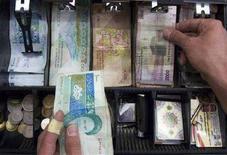 <p>Владелец магазина в Тегеране пересчитывает деньги в кассе. Россия присоединится к экономическим санкциям против Ирана, сообщил Интерфакс, цитируя указ, подписанный бывшим президентом РФ Владимиром Путиным 5 мая 2008 года. (REUTERS/Morteza Nikoubazl)</p>