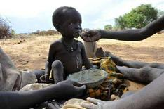 <p>Un bambino ugandese malnutrito viene imboccato. REUTER/James Akena (UGANDA)</p>
