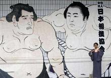 <p>Женщина в кимоно напротив картины, на которой изображены два сумоиста, в Токио 25 мая 2008 года. Ветеран борьбы сумо в приступе ярости ударил своего менее опытного напарника ложкой, за что был наказан сокращением своей заработной платы. (REUTERS/Kim Kyung-Hoon)</p>
