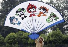 <p>Мужчина держит в руках змея с изображениями пяти символов Олимпиады 2008 года в Пекине 7 августа 2007 года. Наводнения на юге Китая, похоже, стали последним элементом загадочного проклятия, наложенного на страну, и пяти талисманов Олимпийских игр, замешанных в несчастьях КНР. (REUTERS/Jeff Xu)</p>