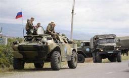 """<p>Российские миротворцы сидят на бронетранспортере на блокпосту около деревни Эгнети в Южной Осетии, 5 августа 2008 года. Российские военные отправили в помощь миротворцам в Южной Осетии """"подкрепление для прекращения кровопролития"""", сообщили российские агентства со ссылкой на официальное сообщение Минобороны РФ. Грузия, со своей стороны, сообщила, что российские самолеты бомбят авиабазу в 25 километрах от Тбилиси. (REUTERS/Irakli Gedenidze)</p>"""