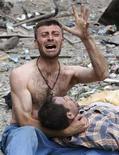 <p>Житель Гори плачет над телом родственника после воздушных атак российских истребителей, 9 августа 2008 года. Российские истребители в субботу сбросили бомбу на многоэтажный дом в грузинском городе Гори, убив по меньшей мере пять человек, сообщил репортер Рейтер с места событий. (REUTERS/Gleb Garanich)</p>