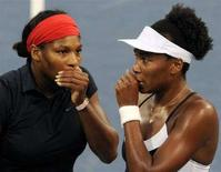 <p>Serena Williams (sinistra) parla con la sorella Venus sul campo, ai Giochi di Pechino. REUTERS/Toby Melville</p>
