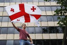 <p>Мужчина с флагом Грузии у здания российской миссии при ЕС в Брюсселе 11 августа 2008 года. Грузия передала в исполком Содружества независимых государств ноту о своем намерении покинуть организацию, начав тем самым официальную процедуру выхода из Содружества, созданного в 1991 и объединившего двенадцать постсоветских государств. (REUTERS/Francois Lenoir)</p>