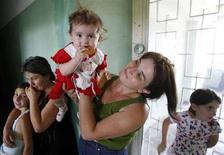 <p>Беженцы из Южной Осетии во временном прибежище в Тбилиси 19 августа 2008 года. Международные организации по оказанию гуманитарной помощи обратились во вторник к властям России с просьбой обеспечить безопасный доступ в Южную Осетию. (REUTERS/Gleb Garanich)</p>