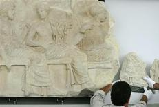 <p>Greek archaeological restorers place a fragment from the Parthenon's frieze, which Italy returned to Greece, during a visit by Italy's President Giorgio Napolitano at the New Acropolis museum in Athens September 24, 2008. REUTERS/John Kolesidis</p>