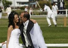 <p>A newlywed Italian couple poses near the Italian Cup cricket final between Azzurra, a team of Pakistani expatriates, and Latina Lanka, a team of Sri Lankans, in Grosseto September 21, 2008. REUTERS/Giampiero Sposito</p>