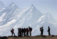 <p>Trekkers pause to admire Mt. Kusum Kangru (6369 mts) in the Mt. Everest region in Nepal March 30, 2006. REUTERS/Gopal Chitrakar.</p>