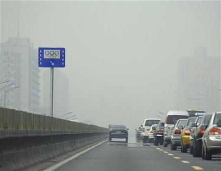 A car drives in an 'Olympic Lane' as other cars remain idle in the remaining lanes along a main road on a hazy day in Beijing, July 28, 2008. REUTERS/David Gray