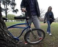 <p>Ignacio Jardon places a bike next to a tree in Buenos Aires, October 3, 2008. REUTERS/Enrique Marcarian</p>