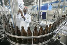<p>Brewer Timothy Gikuhi holds up an empty beer bottle to inspect its cleanliness in Keroche Brewery, Kenya's second brewery situated in the small town of Naivasha, about 84 km (52 miles) from the capital Nairobi, September 2, 2008. REUTERS/Antony Njuguna</p>