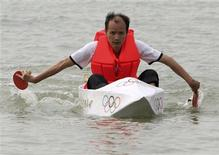 <p>Zhu Yalin uses ping-pong bats to paddle a boat made of paper, and held together with a flour-based glue, near Xiamen, Fujian province, October 13, 2008. Picture taken October 13, 2008. REUTERS/China Daily</p>