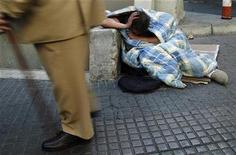 <p>A man walks past a homeless man on the streets of Madrid October 2, 2008. REUTERS/Susana Vera</p>