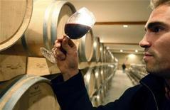 <p>A man looks at a glass of Chateau Larose Trintaudon red wine in Saint Laurent Medoc, near Bordeaux, southwestern France, October 28, 2008. REUTERS/Regis Duvignau</p>