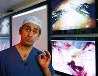<p>Professor Lord Ara Darzi speaks to Reuters about robotic surgery in front of video images of robots performing surgery at Imperial College London October 24, 2008. REUTERS/Luke MacGregor</p>