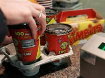 <p>A customer buys coffee and Timbits at a Tim Hortons coffee outlet at the Pengrowth Saddledome in Calgary March 24, 2006. REUTERS/J.P. Moczulski</p>