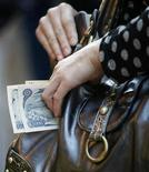 <p>A woman holds money at a shop in Tokyo in this October 16, 2008 file photo. REUTERS/Kim Kyung-Hoon/Files</p>