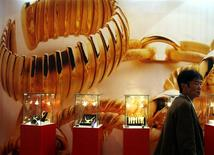 <p>A visitor to the China International Jewellery Fair walks past a poster and gold jewellery display in Beijing November 12, 2008. REUTERS/David Gray</p>