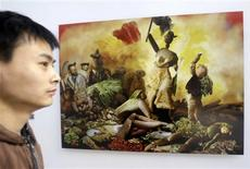 """<p>A visitor stands in front of artist Ju Duoqi's work """"Liberty Leading the Vegetables"""" at his """"The Vegetable Museum"""" exhibition at a photo gallery in Beijing November 25, 2008. REUTERS/Jason Lee</p>"""